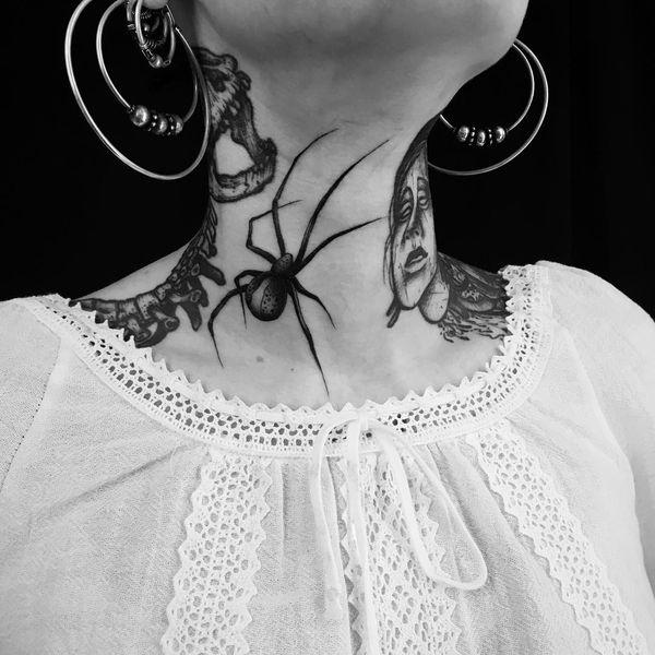 Черная татуировка паука с длинными лапами на шее