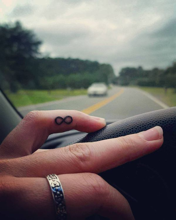 Тату символа бесконечности на безымянном пальце у девушки