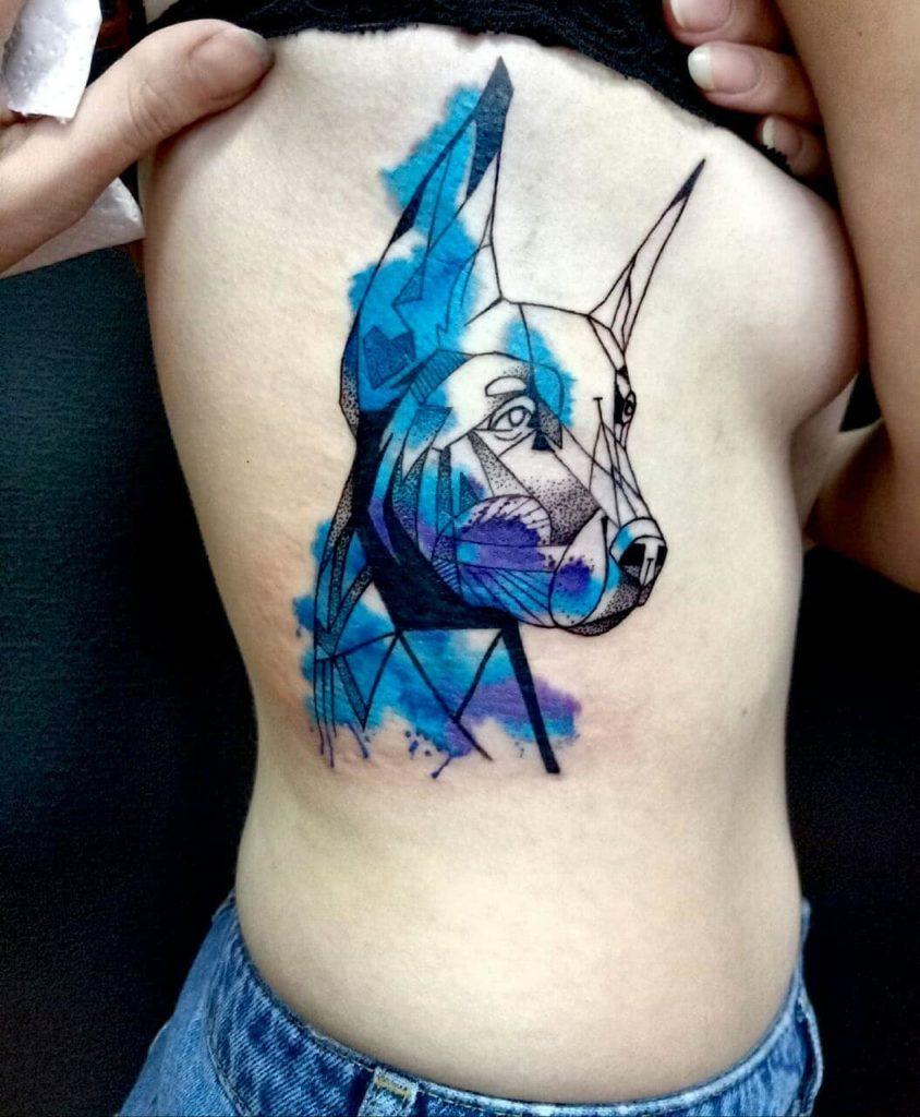 В акварельном стиле тату добермана на ребрах девушки
