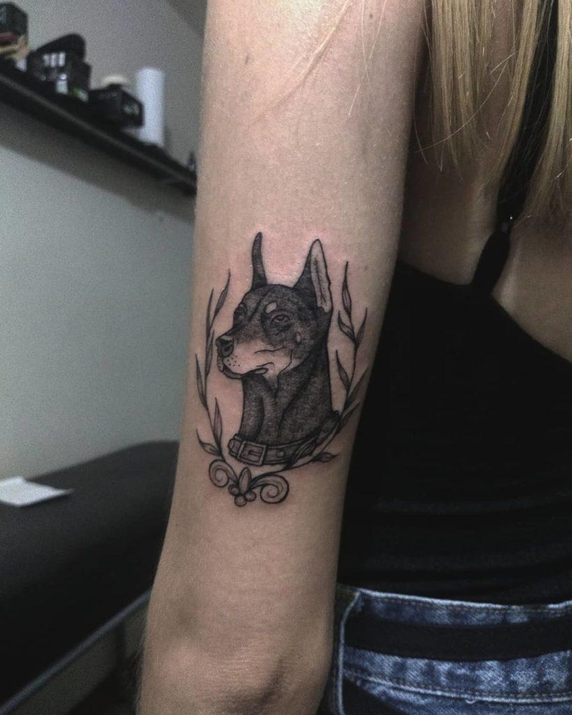 Татуировка добермана в цветах на локте девушки