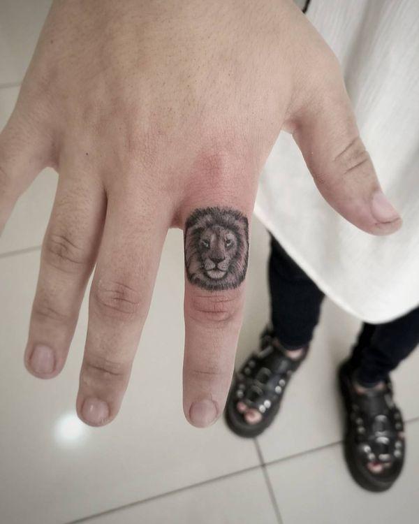 тату лев на пальце