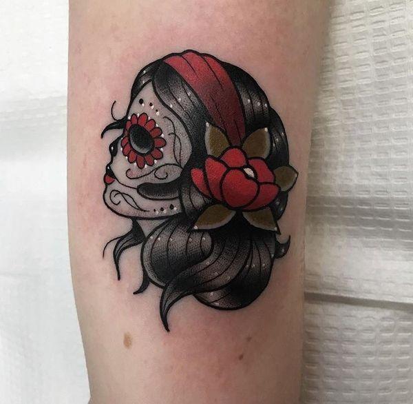 Женская татуировка черепа с красными акцентами