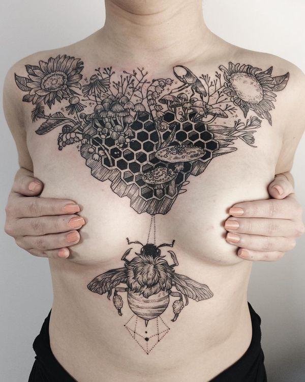 Женская татуировка на груди из пушистого шмеля и соты