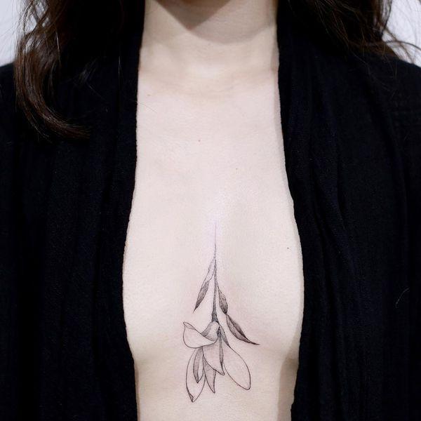 Нежная магнолия в корейской татуировке между грудями