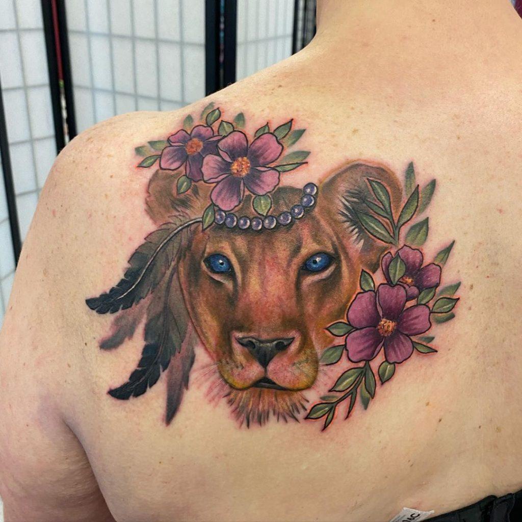 Татуировка львицы в цветах на лопатке
