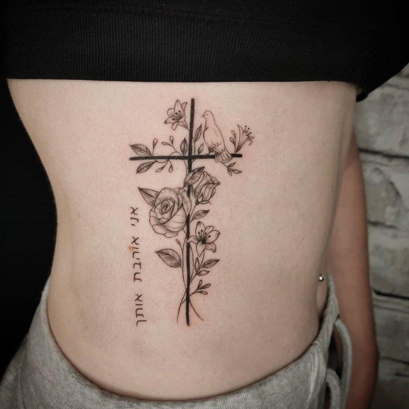 Татуировка креста в цветах с голубем и надписью на иврите