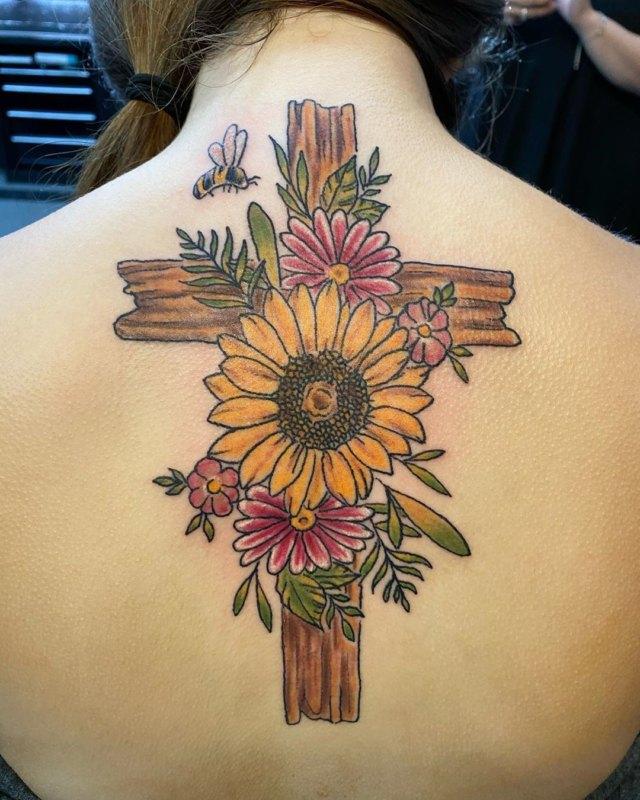Крест с полевыми цветами и пчелой на спине у девушки