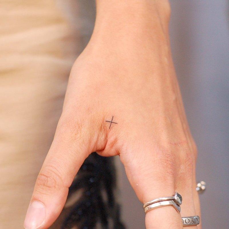 миниатюрный крест между пальцами