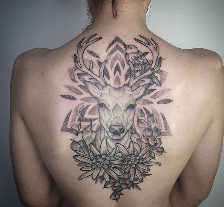 Тату оленя в цветах с птицей на спине у девушки