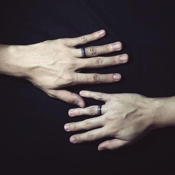 Черная татуировка на пальце руки