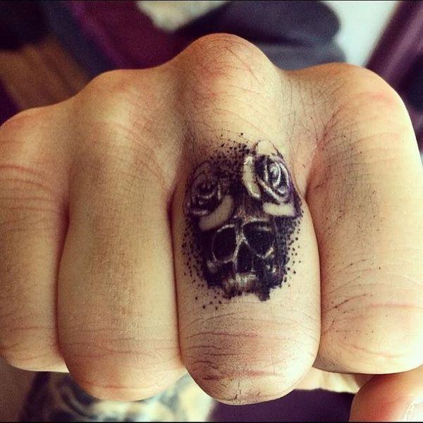 Черно-серая татуировка черепа с двумя розами на пальце