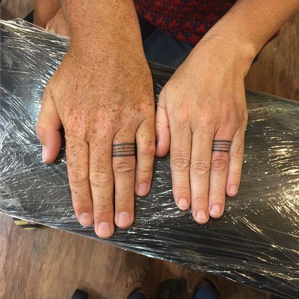 Простые линии свадебных татуировок на безымянных пальцах