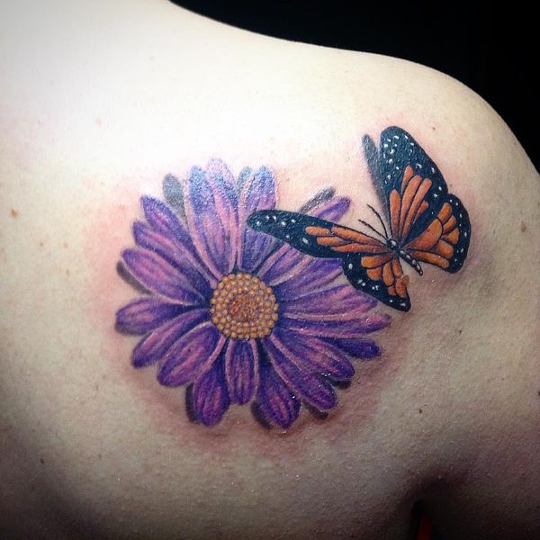 Фиолетовая маргаритка и татуировка бабочка на плече