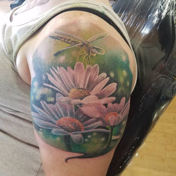 Татуировка ромашки со стрекозой на плече