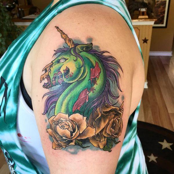 Татуировка зомби-единорога на плече