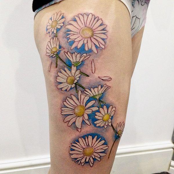 Разнообразие цветков ромашки на татуировке бедра