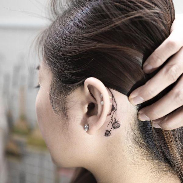 Готическая розовая татуировка за ухом