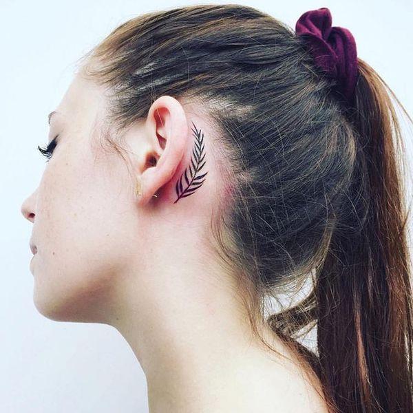 Монохромная татуировка за ухом