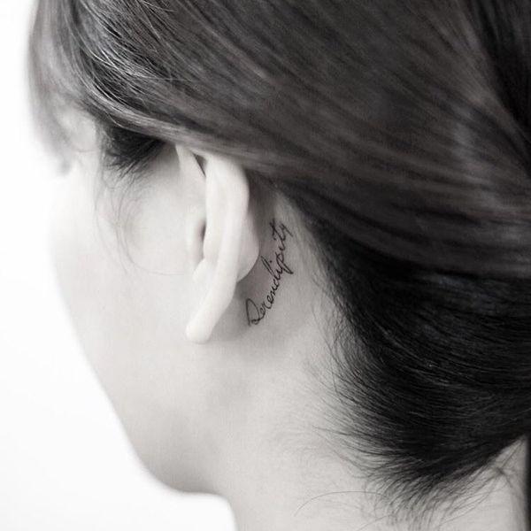 Черно-белая надпись татуировки за ухом