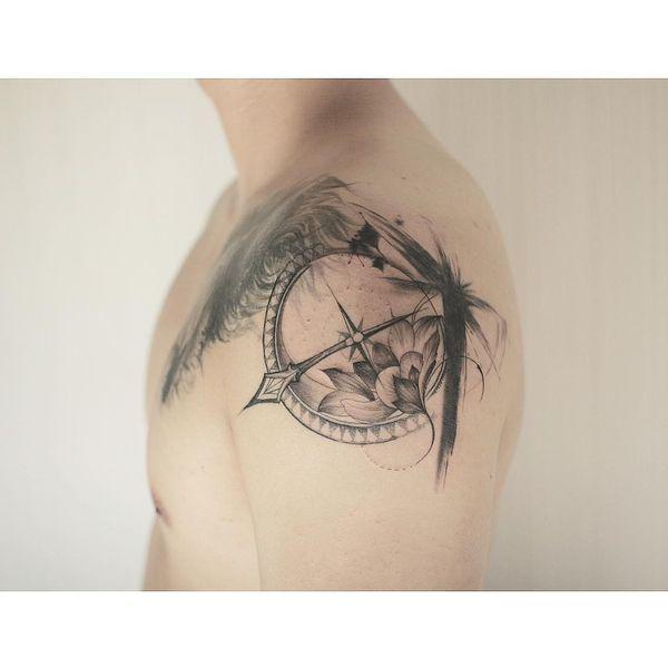 Компас с татуировкой на плече лотоса