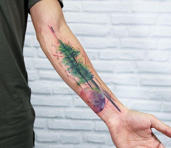 Красочное тату дерево с изображением вселенной на предплечье.