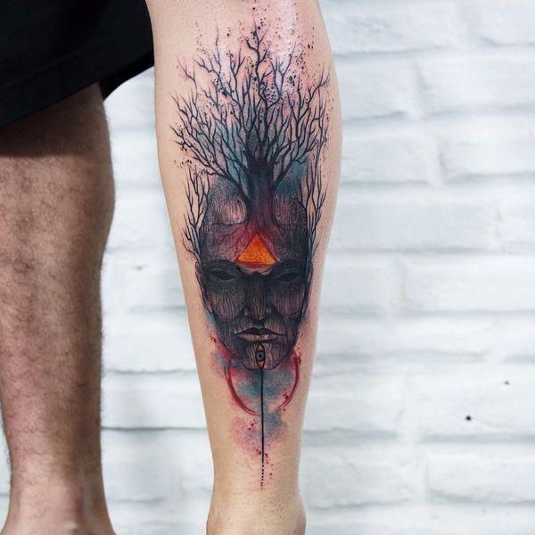 Тату темное дерево с маской на ноге.
