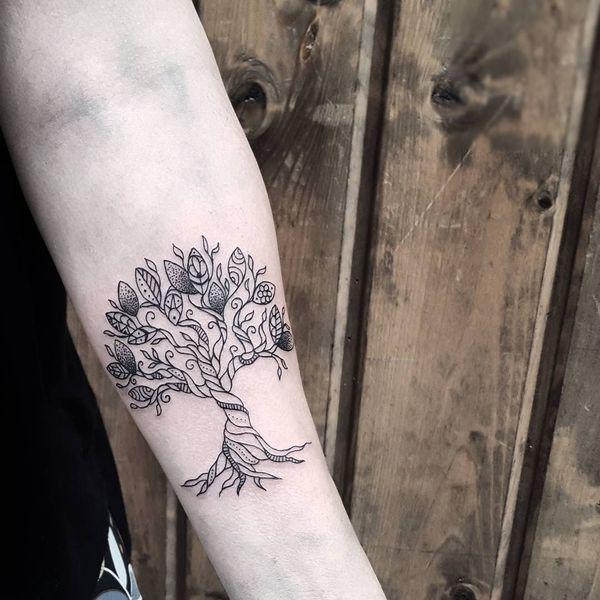 Фантастическая татуировка в виде дерева на предплечье.