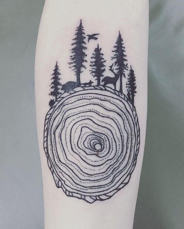 Татуировка на предплечье в виде пня с лесом наверху.