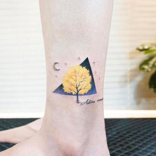 Маленькая татуировка в виде дерева с цитатой на щиколотке.