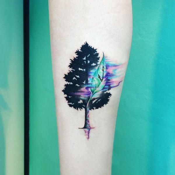Татуировка силуэт дерева с акварельным листом.