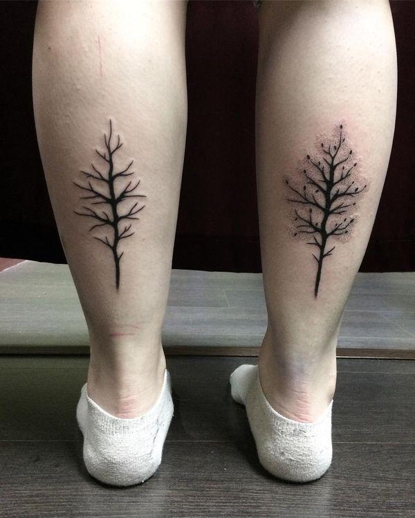 Татуировки с деревом на обоих икрах.