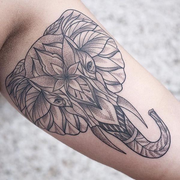Татуировка на бицепсе руками в виде мордочки слона из листьев
