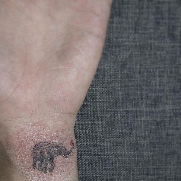Симпатичная татуировка слона на запястье с маленьким символом любви