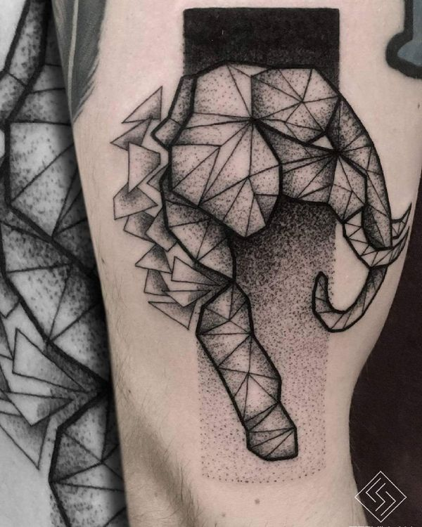 Геометрическая татуировка в стиле дотворк на бицепсе с головой мистического слона