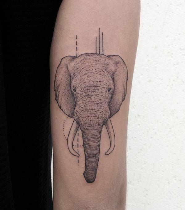 Серая минималистичная татуировка в виде головы слона на руке в стиле дотворк