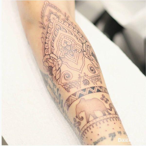 Татуировка в виде силуэта слона на полурукаве, украшенная украшениями