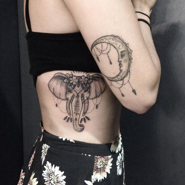 Тату голова слона с цветами на боку у женщины