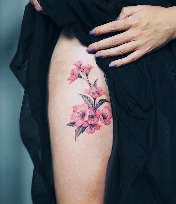 Элегантная татуировка сакуры на бедре