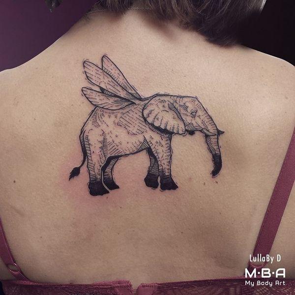 Необычная идея татуировки слона с крыльями на спине для девушки