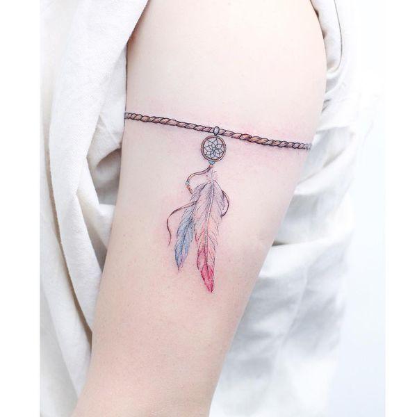 тату синие и розовые перья на руке