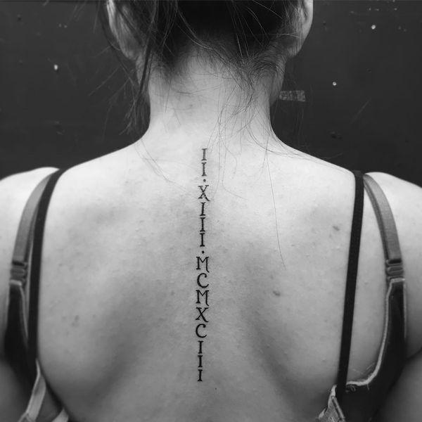 татуировка вдоль позвоночника с римскими цифрами 1993 года для девушки