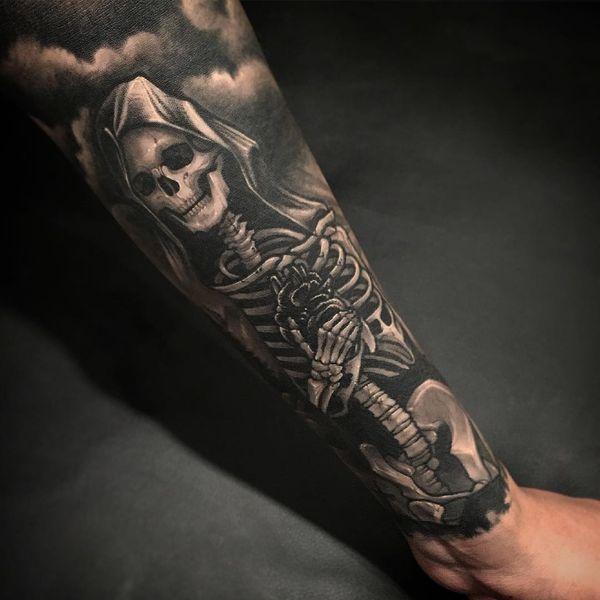 Rad Grim Reaper держит татуировку на рукаве в виде сердца