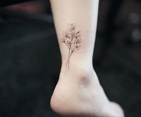 Женственная татуировка сакуры на щиколотке