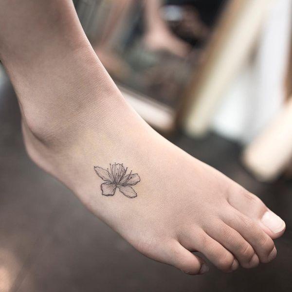 Красивая корейская маленькая татуировка сакуры на ступне